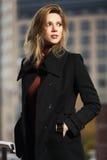 Arbeiten Sie die blonde Frau im schwarzen Mantel gehend auf Stadtstraße um Stockfoto