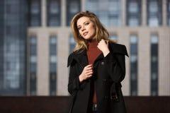 Arbeiten Sie die blonde Frau im schwarzen Mantel gehend auf Stadtstraße um Lizenzfreie Stockbilder