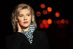 Arbeiten Sie die blonde Frau im schwarzen Mantel gehend in eine Nachtstadtstraße um Stockbilder