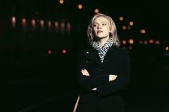 Arbeiten Sie die blonde Frau im schwarzen Mantel gehend in eine Nachtstadtstraße um Lizenzfreie Stockfotos