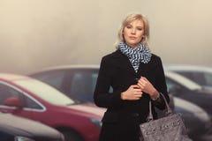 Arbeiten Sie die blonde Frau im schwarzen Mantel gehend in eine Stadtstraße um Stockbilder