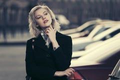 Arbeiten Sie die blonde Frau im schwarzen Mantel gehend in Stadtstraße um Stockfoto