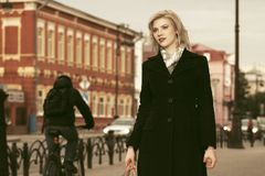 Arbeiten Sie die blonde Frau im schwarzen Mantel gehend in Stadtstraße um Lizenzfreie Stockfotografie