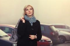 Arbeiten Sie die blonde Frau im schwarzen Mantel gehend in Stadtstraße um Lizenzfreies Stockbild