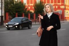 Arbeiten Sie die blonde Frau im schwarzen Mantel gehend in Stadtstraße um Stockbilder