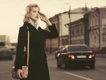 Arbeiten Sie die blonde Frau im schwarzen Mantel mit Handtasche gehend in Stadtstraße um Lizenzfreies Stockfoto