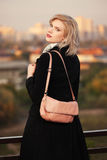Arbeiten Sie die blonde Frau im schwarzen Mantel mit Handtasche gehend in Stadtstraße um Stockfotografie