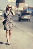 Arbeiten Sie die blonde Frau um, die um Handy auf Stadtstraße ersucht Lizenzfreies Stockbild