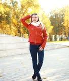 Arbeiten Sie die blonde junge Frau um, die eine rote Lederjacke trägt Lizenzfreies Stockfoto