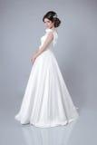 Arbeiten Sie die Brautfrau um, die im Hochzeitskleid aufwirft, das auf grauem BAC lokalisiert wird Lizenzfreies Stockbild