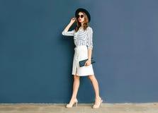 Arbeiten Sie die elegante Frau um, die einen schwarzen Hut und einen Weißrock trägt lizenzfreies stockbild