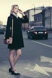 Arbeiten Sie die Frau im schwarzen Mantel mit Handtasche gehend in Stadtstraße um Lizenzfreie Stockbilder
