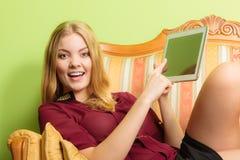 Arbeiten Sie die Frau um, die auf Sofa mit PC-Tablette legt Lizenzfreies Stockbild