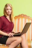 Arbeiten Sie die Frau um, die auf Sofa unter Verwendung des PC-Laptops sitzt Stockbilder