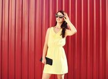 Arbeiten Sie die Frau um, die ein gelbes Kleid und Sonnenbrille mit Handtaschenkupplung über Rot trägt Stockfotografie