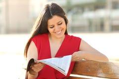Arbeiten Sie die Frau um, die eine Zeitschrift in einem Park liest stockbilder