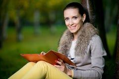 Arbeiten Sie die Frau um, die einen Tablet-Computer draußen im Abendpark verwendet Stockbilder