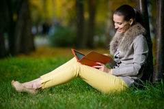 Arbeiten Sie die Frau um, die einen Tablet-Computer draußen im Abendpark verwendet Lizenzfreie Stockbilder