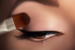 Arbeiten Sie die Frau um, die Lidschatten, Wimperntusche auf Augenlid, Wimper und Augenbraue unter Verwendung der Make-upbürste a stockbild