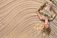 Arbeiten Sie die Frau um, die am Strandsandhintergrund liegt Stockfotografie