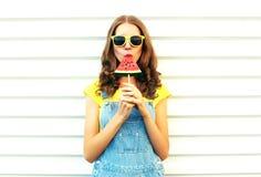 Arbeiten Sie die hübsche Frau um, die eine Scheibe der Wassermelone in Form von Eiscreme auf weißem Hintergrund isst Stockbild
