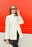 Arbeiten Sie die hübsche Frau um, die eine weiße Manteljacke mit Handtasche über Rot trägt Lizenzfreies Stockfoto