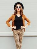 Arbeiten Sie die hübsche Frau um, die schwarzen Hut, Sonnenbrille und Jacke über städtischem Hintergrund trägt Stockfotos