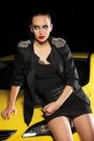 Arbeiten Sie die junge Frau um, die auf einem Auto in der Nacht sitzt Lizenzfreie Stockbilder