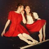 Arbeiten Sie die kaukasischen Ballerinen um, die auf dem Klavier und dem Lachen sitzen lizenzfreies stockfoto