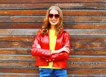Arbeiten Sie die lächelnde Frau des Herbstes um, die eine rote Lederjacke trägt stockfotografie