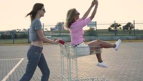 Arbeiten Sie die lustigen jungen Hippie-Mädchen, die Spaß am Einkaufszentrumparken haben um, rollen Sie sich im Warenkorb auf Str stock footage