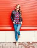 Arbeiten Sie die recht junge blonde lächelnde Frau um, die eine schwarze Felsenart trägt, die über buntem Rot aufwirft Lizenzfreie Stockbilder
