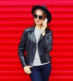 Arbeiten Sie die recht junge Frau um, die auf dem Smartphone spricht, der schwarze Felsenart über buntem Rot trägt Stockbild