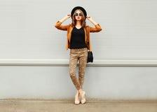 Arbeiten Sie die recht junge Frau um, die einen Retro- eleganten Hut, eine Sonnenbrille, eine braune Jacke und eine schwarze Hand Stockfotografie