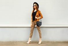 Arbeiten Sie die recht junge Frau um, die einen Retro- eleganten Hut, eine Sonnenbrille, eine braune Jacke und eine schwarze Hand Lizenzfreies Stockfoto