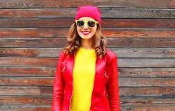Arbeiten Sie die recht lächelnde Frau um, die einen roten Lederjackehut im Herbst über hölzernem trägt lizenzfreie stockfotografie