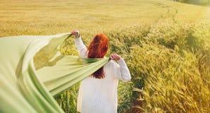 Arbeiten Sie die rote Haarfrau um, die zurück steht, übergibt oben mit grünem Gewebe Lizenzfreie Stockfotos