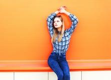 Arbeiten Sie die schöne blonde dünne Frau um, die auf buntem orange Hintergrund aufwirft Lizenzfreie Stockfotos