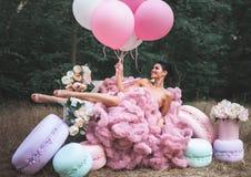 Arbeiten Sie die sexy Frau um, die im rosa erstaunlichen Kleid gekleidet wird, das von den Franzosen Macarons umgeben wird stockbilder