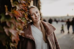 Arbeiten Sie draußen die blonde junge Frau um, die auf dem magischen Herbstlaub auf Hintergrund nahe Gebäude auf der Straße aufwi Stockfotografie