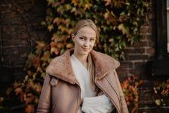 Arbeiten Sie draußen die blonde junge Frau um, die auf dem magischen Herbstlaub auf Hintergrund nahe Gebäude auf der Straße aufwi Lizenzfreies Stockbild