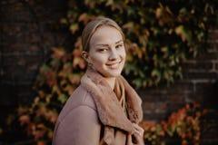 Arbeiten Sie draußen die blonde junge Frau um, die auf dem magischen Herbstlaub auf Hintergrund nahe Gebäude auf der Straße aufwi Lizenzfreie Stockfotos