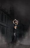 Arbeiten Sie Eintragfaden einer Frau in einem langen schwarzen Kleid um stockbilder