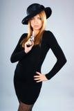 Arbeiten Sie Eintragfaden einer jungen Frau in einem schwarzen Kleid um Lizenzfreie Stockfotografie