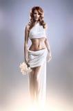 Arbeiten Sie Eintragfaden einer jungen Redheadfrau in einem Kleid um Stockfotos