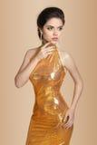Arbeiten Sie elegante Brunettefrau im goldenen Kleid um, das auf Beige lokalisiert wird Lizenzfreie Stockfotos