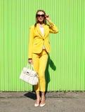 Arbeiten Sie elegante junge Frau in der gelben Klagenkleidung mit Handtasche um Lizenzfreies Stockbild
