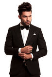 Arbeiten Sie eleganten Mann im Smoking um, das seinen Ärmel repariert Lizenzfreies Stockfoto