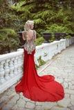 Arbeiten Sie elegantes blondes Frauenmodell im roten Kleid mit langem Zug von um Stockfotos