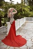 Arbeiten Sie elegantes blondes Frauenmodell im roten Kleid mit langem Zug von um Stockbild